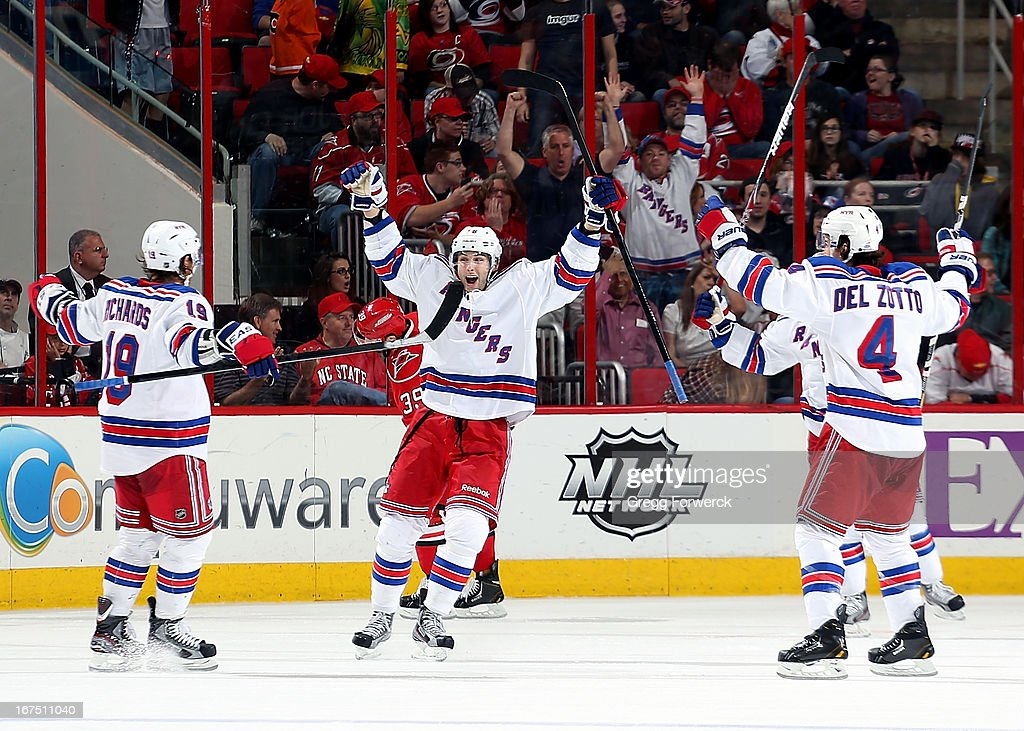Brad Richards #19 of the New York Rangers celebrates his power play goal against the Carolina Hurricanes to tie the game 3-3 late in the third period with teammates Derick Brassard #16 and Michel Del Zotto #4 during their NHL game at PNC Arena on April 25, 2013 in Raleigh, North Carolina.