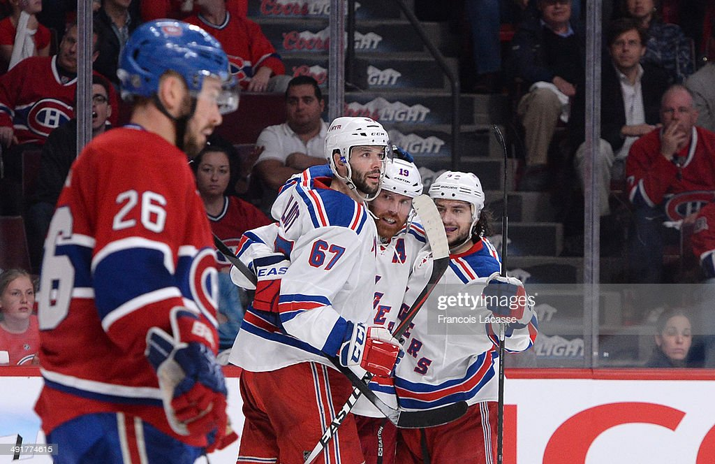 <a gi-track='captionPersonalityLinkClicked' href=/galleries/search?phrase=Brad+Richards&family=editorial&specificpeople=202622 ng-click='$event.stopPropagation()'>Brad Richards</a> #19 of the New York Rangers celebrates with teammates <a gi-track='captionPersonalityLinkClicked' href=/galleries/search?phrase=Benoit+Pouliot&family=editorial&specificpeople=879830 ng-click='$event.stopPropagation()'>Benoit Pouliot</a> #67 and <a gi-track='captionPersonalityLinkClicked' href=/galleries/search?phrase=Daniel+Carcillo&family=editorial&specificpeople=2116181 ng-click='$event.stopPropagation()'>Daniel Carcillo</a> #13 after scoring a goal against the Montreal Canadiens in Game One of the Eastern Conference Final during the 2014 Stanley Cup Playoffs at the Bell Centre on May 17, 2014 in Montreal, Quebec, Canada.