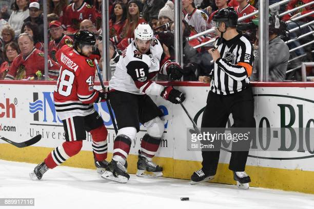 Brad Richardson of the Arizona Coyotes and Vinnie Hinostroza of the Chicago Blackhawks chase the puck in the third period at the United Center on...