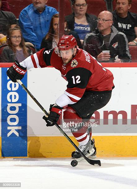 Brad Richardson of the Arizona Coyotes skates the puck up ice against the Vancouver Canucks at Gila River Arena on February 10 2016 in Glendale...