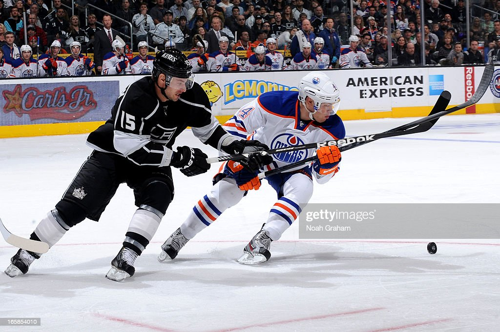 Brad Richardson #15 of the Los Angeles Kings battles for the puck against Taylor Hall #4 of the Edmonton Oilers at Staples Center on April 6, 2013 in Los Angeles, California.