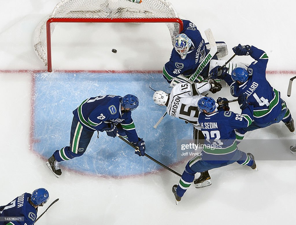 Brad Richardson #15 of the Los Angeles Kings scores the tying goal against Cory Schneider #35 of the Vancouver Canucks despite checking of Alexander Edler #23, Keith Ballard #4 and Henrik Sedin #33 of the Canucks during Game Five of the Western Conference Quarterfinals during the 2012 NHL Stanley Cup Playoffs at Rogers Arena on April 22, 2012 in Vancouver, British Columbia, Canada. Los Angeles won 2-1 in overtime to take the series 4-1.