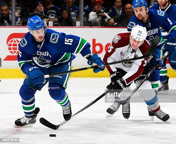 Brad Richardson of the Vancouver Canucks and Cody McLeod of the Colorado Avalanche battle for a loose puck during their NHL game at Rogers Arena...