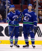 Brad Richardson of the Vancouver Canucks celebrates with David Booth after scoring a goal during NHL action against the Winnipeg Jets on December 22...