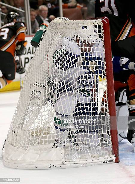 Brad Richardson of the Vancouver Canucks finds himself completely inside the net behind goalie Rederik Andersen of the Anaheim Ducks at Honda Center...