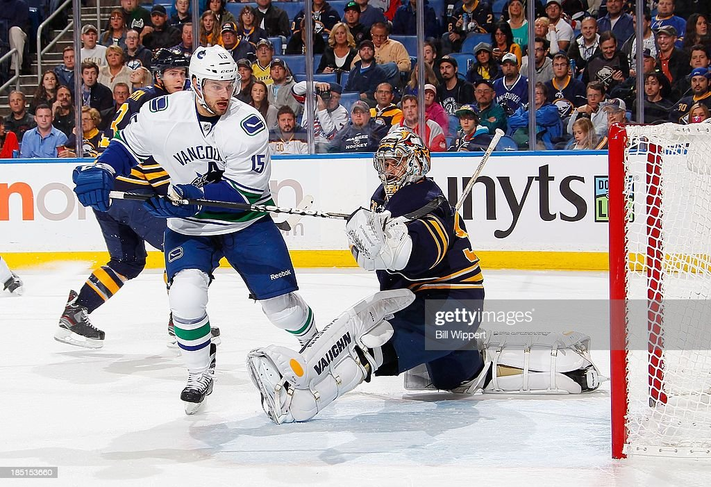 Brad Richardson #15 of the Vancouver Canucks knocks the puck out of the air to score a second-period shorthanded goal against Ryan Miller #30 of the Buffalo Sabres on October 17, 2013 at the First Niagara Center in Buffalo, New York.
