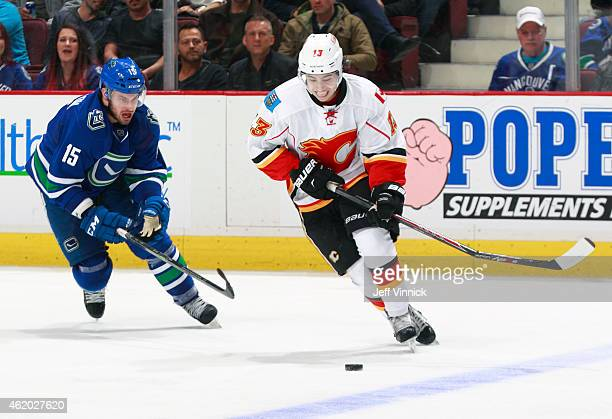 Brad Richardson of the Vancouver Canucks looks on as Johnny Gaudreau of the Calgary Flames skates up ice with a broken stick during their NHL game at...