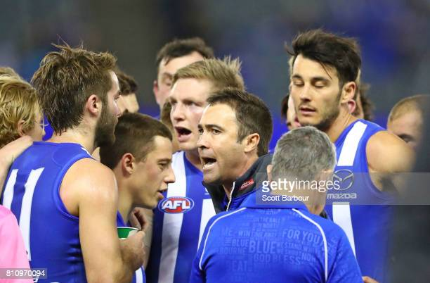 Brad Scott coach of the Kangaroos speaks to his team during a quarter time break with Jack Ziebell of the Kangaroos during the round 16 AFL match...