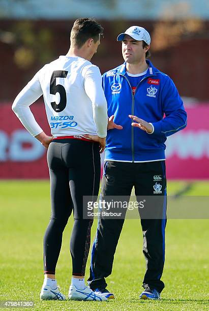 Brad Scott coach of the Kangaroos speaks with Ben Jacobs during a North Melbourne Kangaroos AFL training session at Arden Street Ground on July 8...