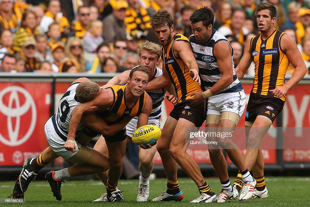 Brad Sewell of the Hawks handballs whilst being tackled by Taylor Hunt of the Cats during the round one AFL match between the Hawthorn Hawks and the Geelong Cats at the Melbourne Cricket Ground on April 1, 2013 in Melbourne, Australia.