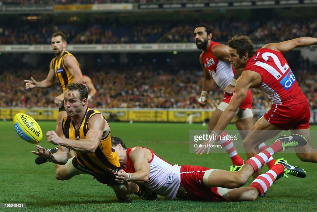 Brad Sewell of the Hawks handballs whilst being tackled during the round seven AFL match between the Hawthorn Hawks and the Sydney Swans at Melbourne Cricket Ground on May 11, 2013 in Melbourne, Australia.