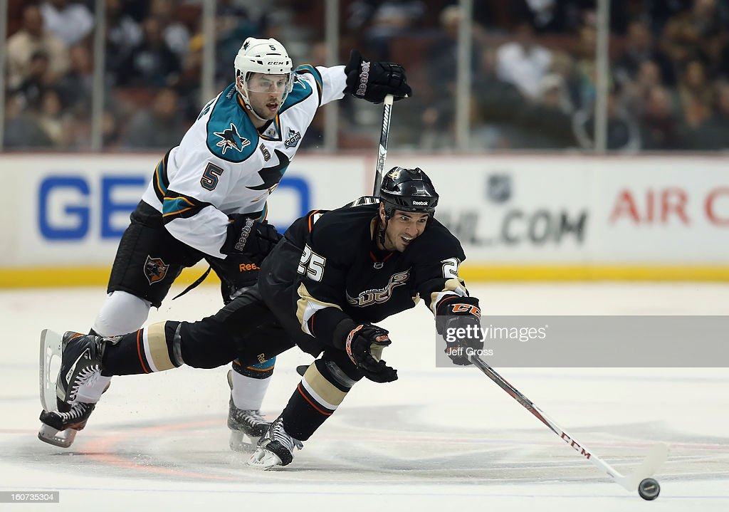 Brad Staubitz #25 of the Anaheim Ducks lunges for the puck while defended by Jason Demers #5 of the San Jose Sharks in the first period at Honda Center on February 4, 2013 in Anaheim, California.