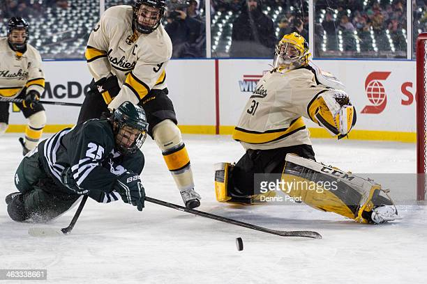 Brad Stebner and Pheonix Copley of the Michigan Tech Huskies defend the net against Brent Darnell of the Michigan State Spartans on December 27 2013...