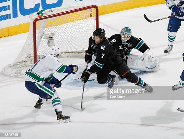 Brad Stuart and Antti Niemi of the San Jose Sharks defend the net against Mason Raymond of the Vancouver Canucks in Game Four of the Western...