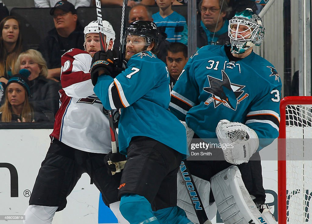 Brad Stuart #7 and Antti Niemi #31 of the San Jose Sharks protects the net against Ryan O'Reily #90 of the Colorado Avalanche during an NHL game on December 23, 2013 at SAP Center in San Jose, California.