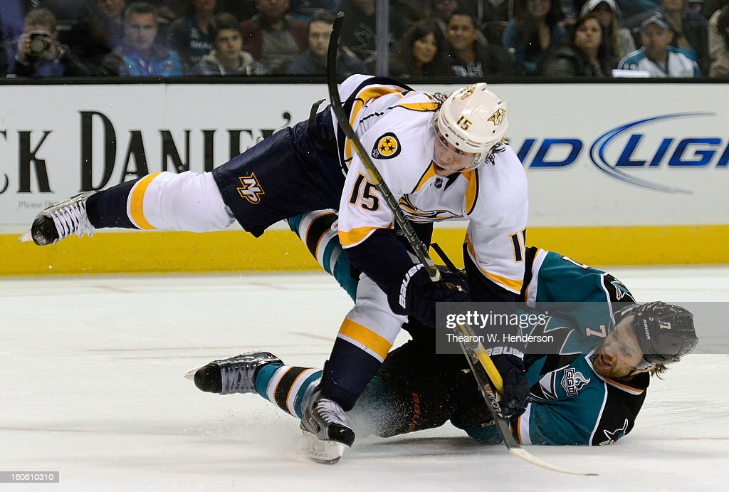 Brad Stuart #7 of the San Jose Sharks fall to the ice attempting to slap the puck away from Craig Smith #15 of the Nashville Predators in the second period of their game at HP Pavilion on February 2, 2013 in San Jose, California.