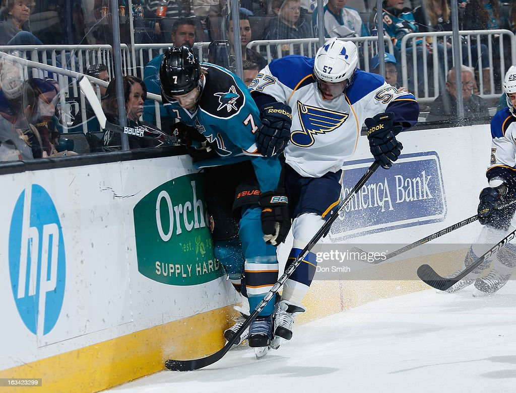 Brad Stuart #7 of the San Jose Sharks fights for the puck against David Perron #57 of the St. Louis Blues during an NHL game on March 9, 2013 at HP Pavilion in San Jose, California.