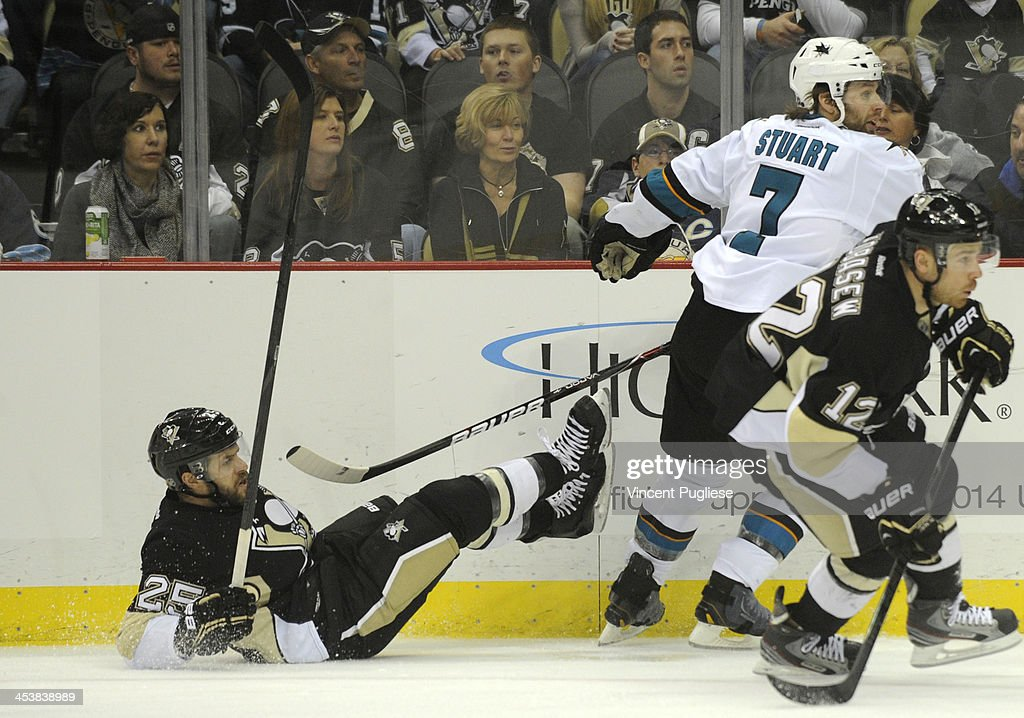 Brad Stuart of the San Jose Sharks knocks down Andrew Ebbett of the Pittsburgh Penguins during the first period on December 5 2013 at the CONSOL...