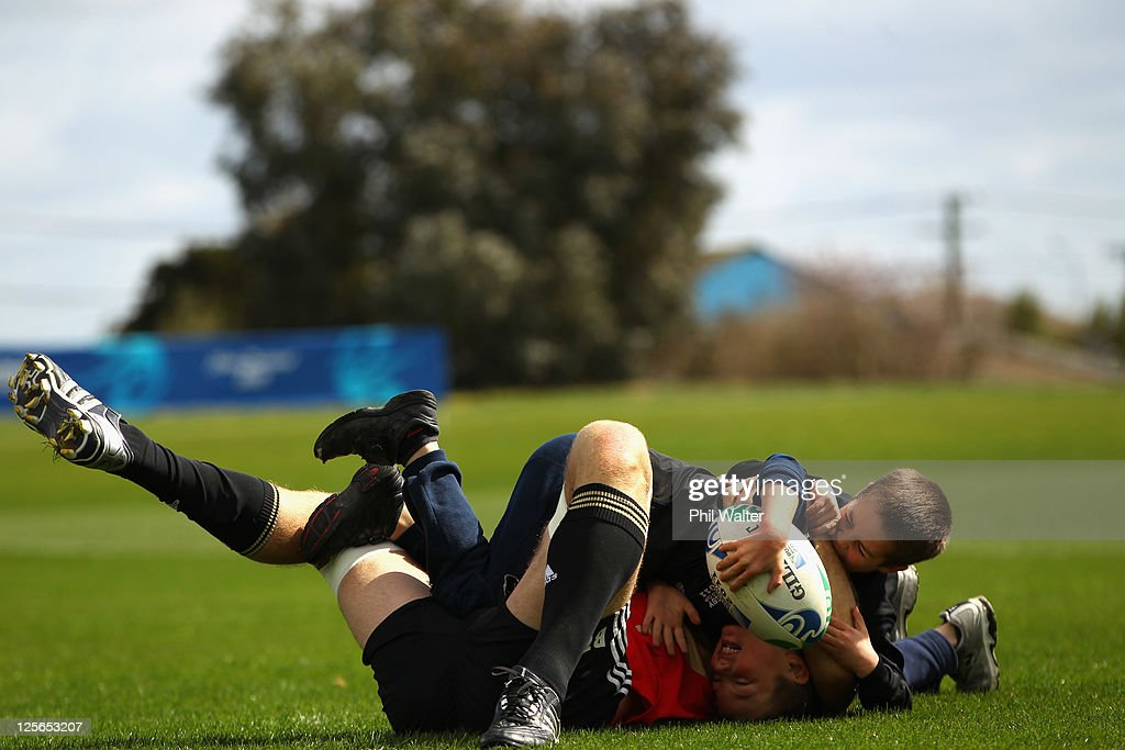 Brad Thorn of the All Blacks plays with children on the field following a New Zealand All Blacks IRB Rugby World Cup 2011 training session at...