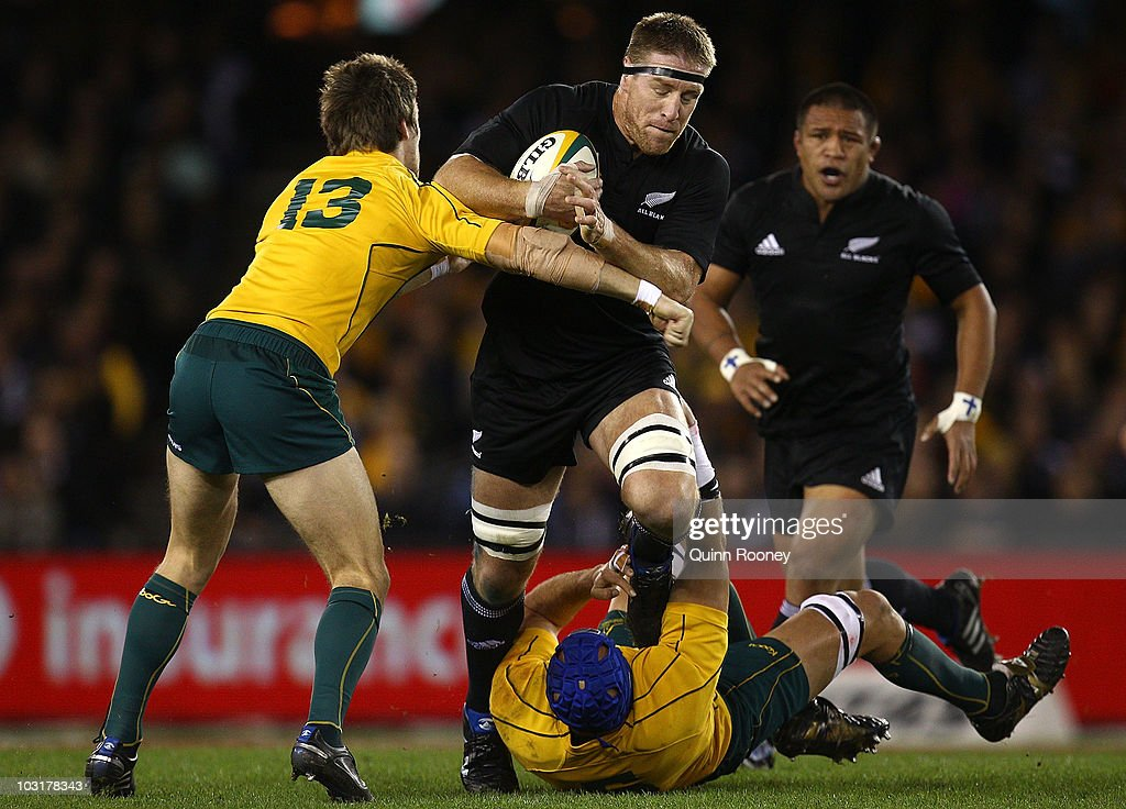 Brad Thorne of the All Blacks is tackled by Nathan Sharpe and Rob Horne of the Wallabies during the 2010 TriNations Bledisloe Cup match between the...