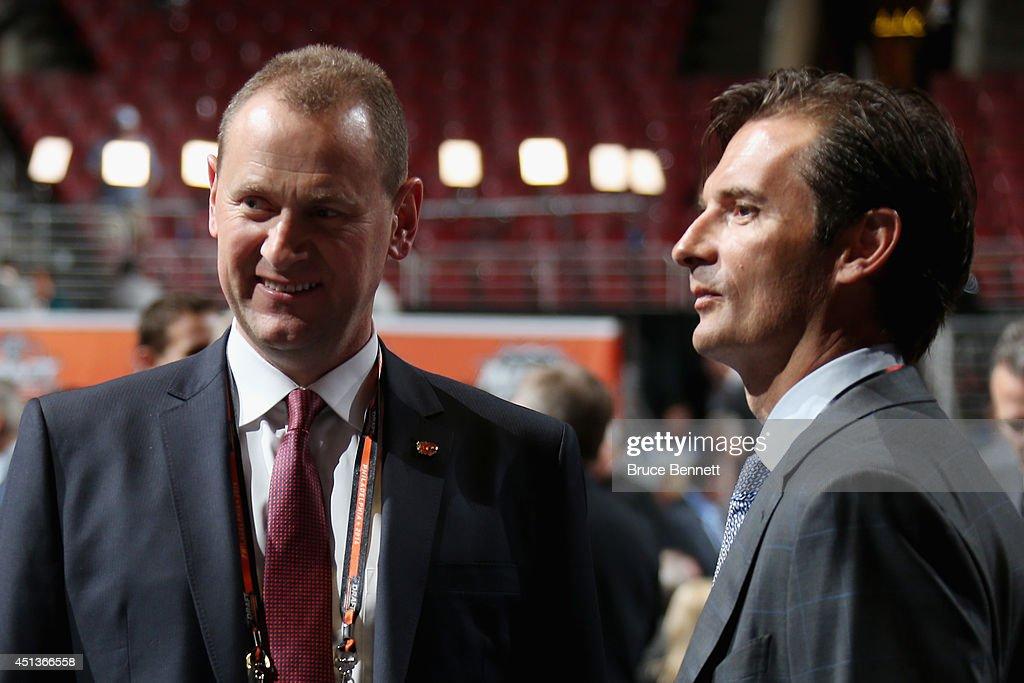 Brad Treliving, General Manager of the Calgary Flames, talks with <a gi-track='captionPersonalityLinkClicked' href=/galleries/search?phrase=Dallas+Eakins&family=editorial&specificpeople=714367 ng-click='$event.stopPropagation()'>Dallas Eakins</a>, head coach of the Edmonton Oilers, prior to the start of the first round of the 2014 NHL Draft at the Wells Fargo Center on June 27, 2014 in Philadelphia, Pennsylvania.