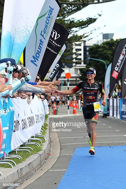 Braden Currie enjoying the fan support as he comes down the finishing chute to win the Port Tauranga 1/2 Ironman Triathlon on January 9 2016 in...