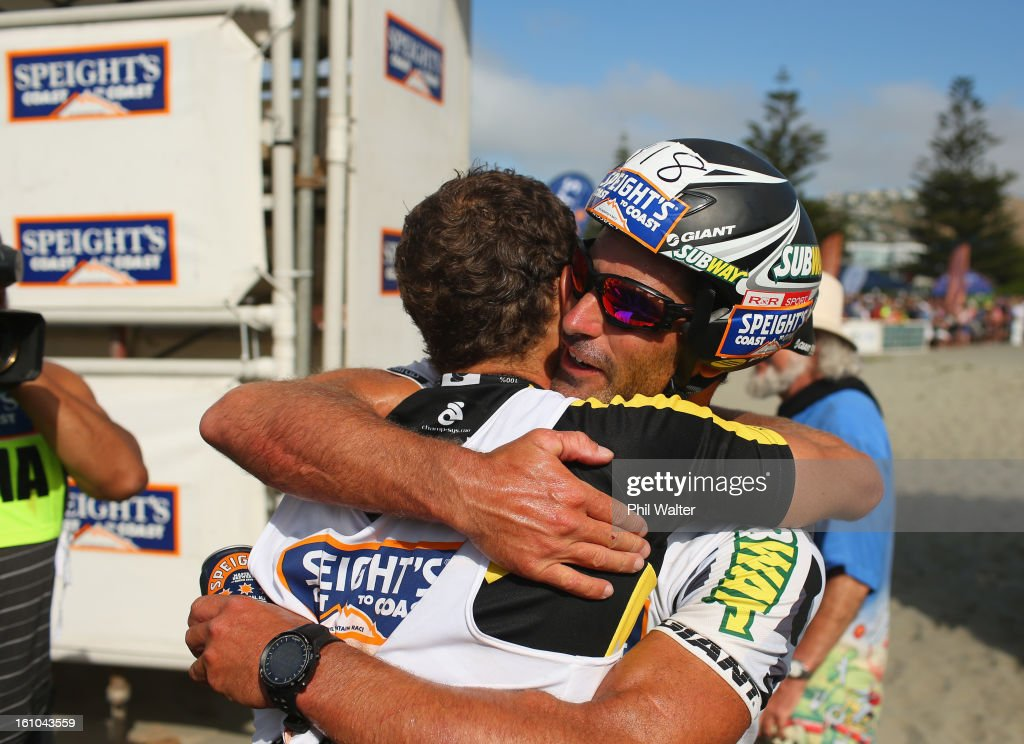 Braden Currie of New Zealand (L) is hugged by Richard Ussher of New Zealand (R) after winning the one day individual event during the 2013 Speights Coast to Coast on February 9, 2013 in Christchurch, New Zealand.