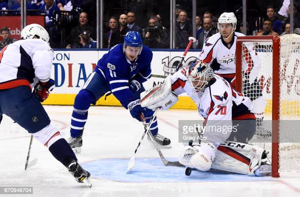 Braden Holtby of the Washington Capitals covers the puck as Zach Hyman of the Toronto Maple Leafs reaches in during the first period in Game Four of...