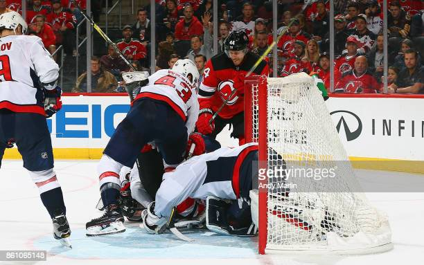 Braden Holtby of the Washington Capitals defends his net with traffic in his crease against the New Jersey Devils during the game at Prudential...