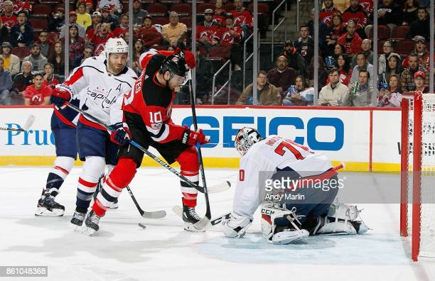 Braden Holtby of the Washington Capitals defends the net as Jimmy Hayes of the New Jersey Devils battles for position during the game at Prudential...