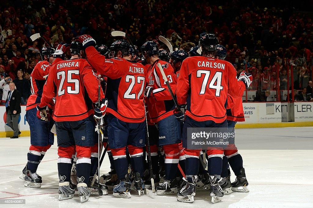 Braden Holtby #70 of the Washington Capitals is congratulated by his teammates after the Capitals defeated the Montreal Canadiens 3-2 in an overtime shootout during an NHL game at Verizon Center on November 29, 2013 in Washington, DC.