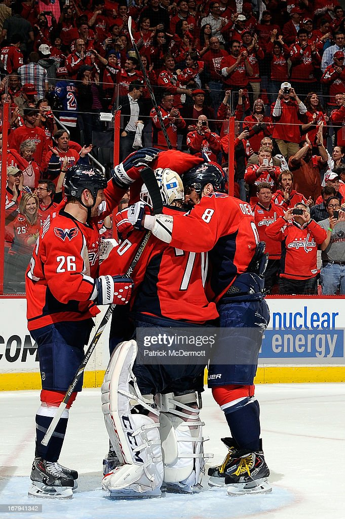 <a gi-track='captionPersonalityLinkClicked' href=/galleries/search?phrase=Braden+Holtby&family=editorial&specificpeople=5370964 ng-click='$event.stopPropagation()'>Braden Holtby</a> #70 of the Washington Capitals is congratulated by teammate <a gi-track='captionPersonalityLinkClicked' href=/galleries/search?phrase=Matt+Hendricks&family=editorial&specificpeople=4537275 ng-click='$event.stopPropagation()'>Matt Hendricks</a> #26 and Alex Ovechkin #8 following the Capitals 3-1 victory in Game One of the Eastern Conference Quarterfinals during the 2013 NHL Stanley Cup Playoffs at Verizon Center on May 2, 2013 in Washington, DC.