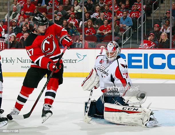 Braden Holtby of the Washington Capitals makes a glove save as Michael Ryder of the New Jersey Devils looks for the rebound during the game at the...