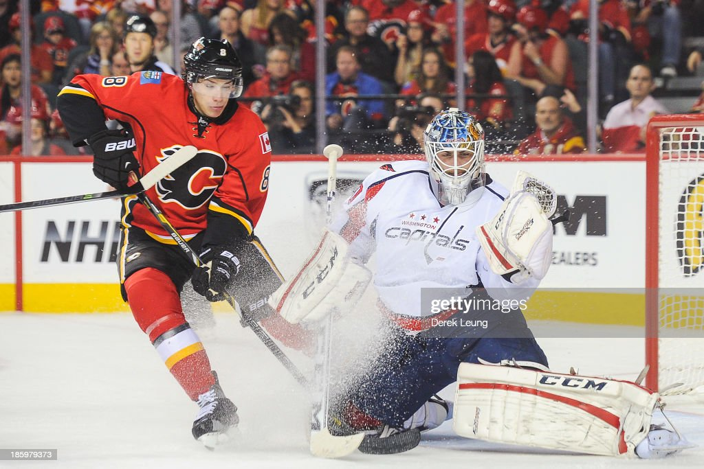 Braden Holtby #70 of the Washington Capitals makes a glove save in front of Joe Colborne #8 of the Calgary Flames during an NHL game at Scotiabank Saddledome on October 26, 2013 in Calgary, Alberta, Canada.