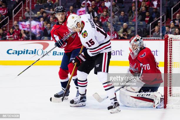 Braden Holtby of the Washington Capitals makes a save as John Carlson and Artem Anisimov of the Chicago Blackhawks battle in front of the net in the...