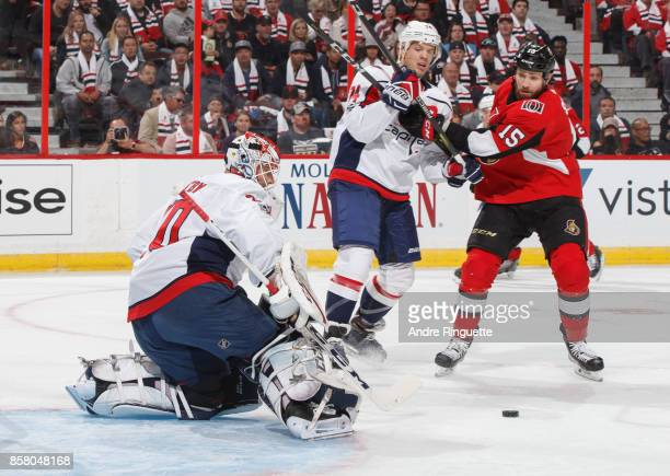Braden Holtby of the Washington Capitals makes a save as teammate John Carlson battles for position against Zack Smith of the Ottawa Senators at...