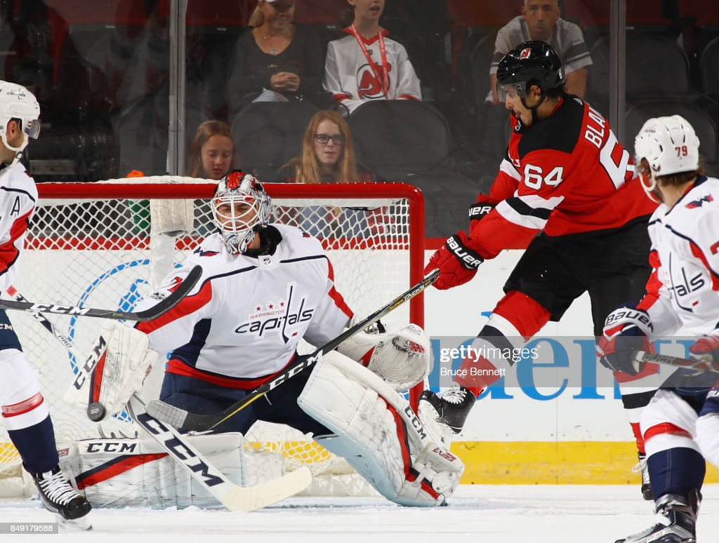 Braden Holtby #70 of the Washington Capitals makes the blocker save as Joseph Blandisi #64 of the New Jersey Devils looks for a rebound during the first period during a preseason game at the Prudential Center on September 18, 2017 in Newark, New Jersey.