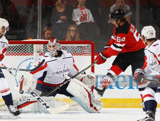 Braden Holtby of the Washington Capitals makes the blocker save as Joseph Blandisi of the New Jersey Devils looks for a rebound during the first...