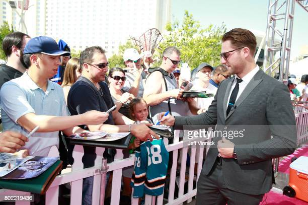 Braden Holtby of the Washington Capitals signs an autograph as he arrives on the magenta carpet for the 2017 NHL Awards at TMobile Arena on June 21...