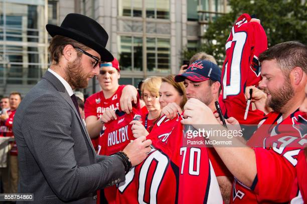 Braden Holtby of the Washington Capitals signs autographs for fans on the Rock the Red Carpet prior to the start of a game against the Montreal...