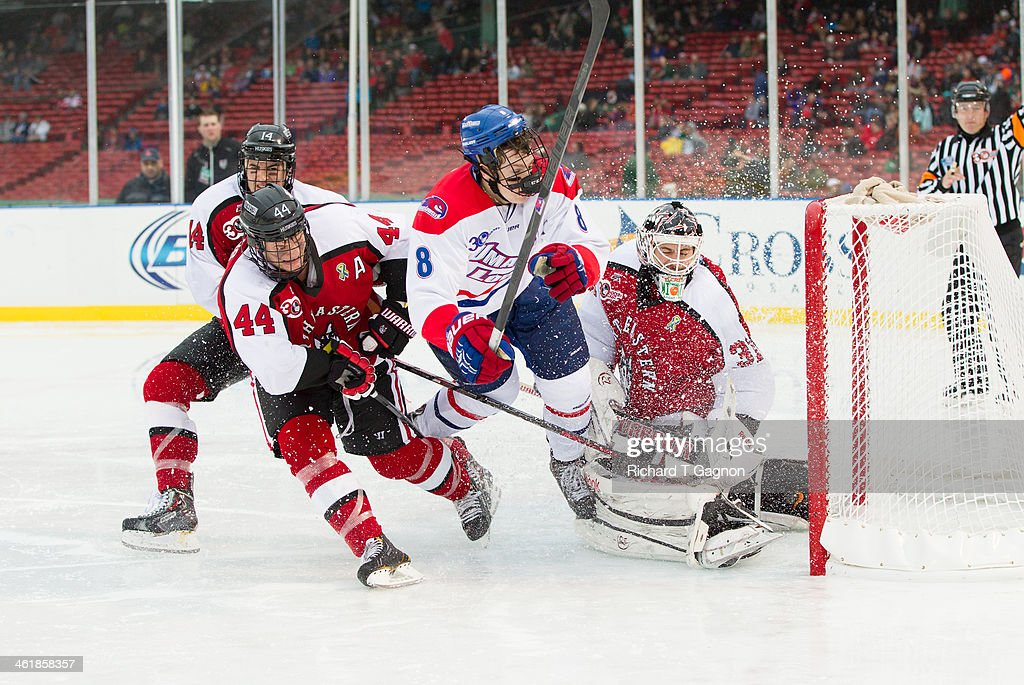 Braden Pimm #14, Dax Lauwers #44 and Clay Witt #31 of the Northeastern University Huskies crash the net with Evan Campbell #8 of the Massachusetts Lowell River Hawks as the water and slush fly through the air during NCAA hockey action in the 'Citi Frozen Fenway 2014' at Fenway Park on January 11, 2014 in Boston, Massachusetts.