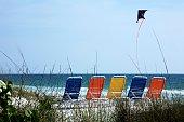 Bradenton Beach, Florida, USA; Beach chairs lined on beach and a kite flying