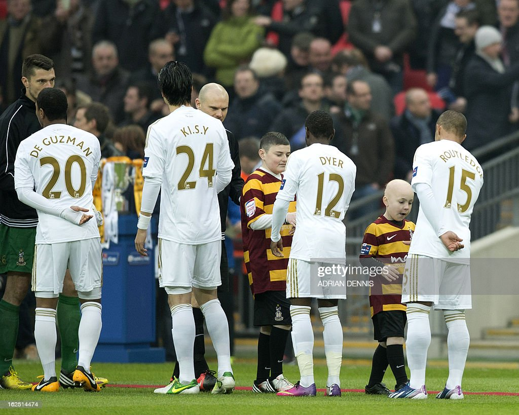 "Bradford City's 9 year old mascot, cancer survivor Jake Turton (2nd R) and his brother (4th R) meet the players before the League Cup final football match between Bradford City and Swansea City at Wembley Stadium in London, England on February 24, 2013. AFP PHOTO/ADRIAN DENNIS USE. No use with unauthorized audio, video, data, fixture lists, club/league logos or ""live"" services. Online in-match use limited to 45 images, no video emulation. No use in betting, games or single club/league/player publications."