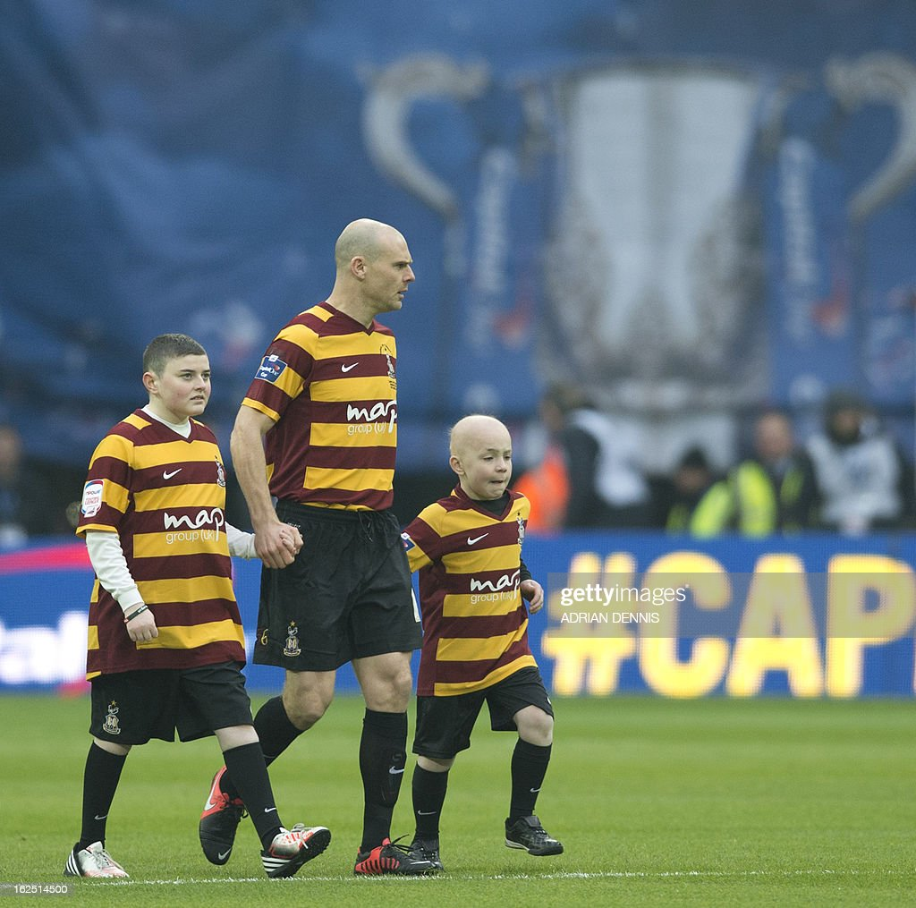 "Bradford City's 9 year old mascot, cancer survivor Jake Turton (R) and his brother (L) walk out with Bradford City's English midfielder Gary Jones (2nd L) before the League Cup final football match between Bradford City and Swansea City at Wembley Stadium in London, England on February 24, 2013. AFP PHOTO/ADRIAN DENNIS USE. No use with unauthorized audio, video, data, fixture lists, club/league logos or ""live"" services. Online in-match use limited to 45 images, no video emulation. No use in betting, games or single club/league/player publications."