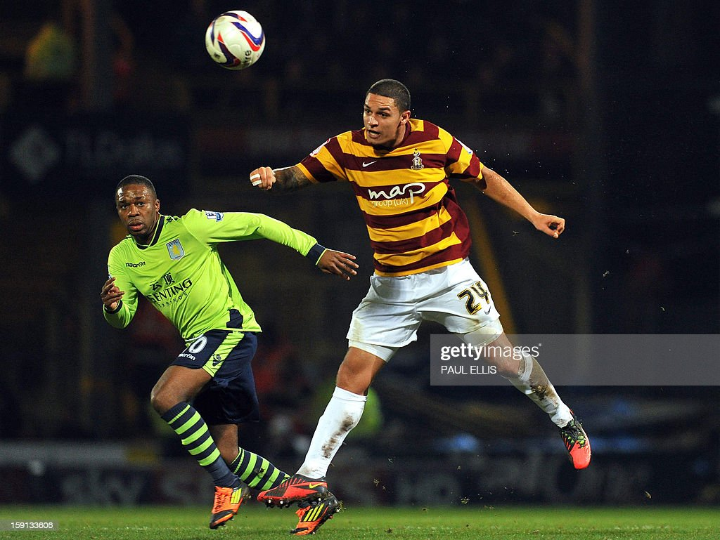"""Bradford City's English midfielder Nathan Doyle (R) heads the ball away from Aston Villa's Belgian striker Christian Benteke during the English League Cup first leg semi-final football match between Bradford City and Aston Villa at The Coral Windows Stadium in Bradford, England, on January 8, 2013. Bradford won the match 3-1. USE. No use with unauthorized audio, video, data, fixture lists, club/league logos or """"live"""" services. Online in-match use limited to 45 images, no video emulation. No use in betting, games or single club/league/player publications."""