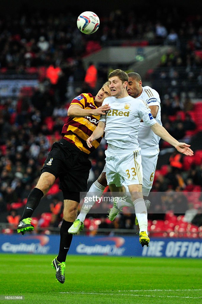 "Bradford City's English striker James Hanson (L) vies with Swansea City's English-born Welsh defender Ashley Williams (R) and Swansea City's Welsh defender Ben Davies during the League Cup final football match between Bradford City and Swansea City at Wembley Stadium in London, England on February 24, 2013. Swansea City won the game 5-0. AFP PHOTO/GLYN KIRK USE. No use with unauthorized audio, video, data, fixture lists, club/league logos or ""live"" services. Online in-match use limited to 45 images, no video emulation. No use in betting, games or single club/league/player publications."