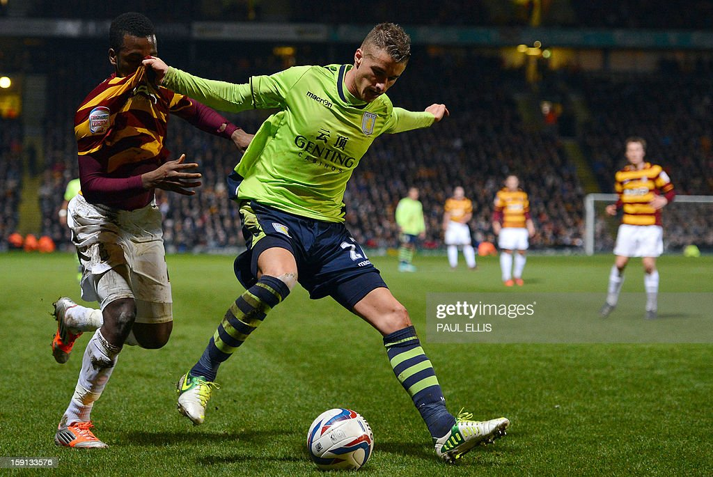 """Bradford City's Jamaican-born English forward Zavon Hines (L) is challenged by Aston Villa's Joe Bennett during the English League Cup first leg semi-final football match between Bradford City and Aston Villa at The Coral Windows Stadium in Bradford, England, on January 8, 2013. Bradford won the match 3-1. AFP PHOTO/PAUL ELLIS USE. No use with unauthorized audio, video, data, fixture lists, club/league logos or """"live"""" services. Online in-match use limited to 45 images, no video emulation. No use in betting, games or single club/league/player publications."""