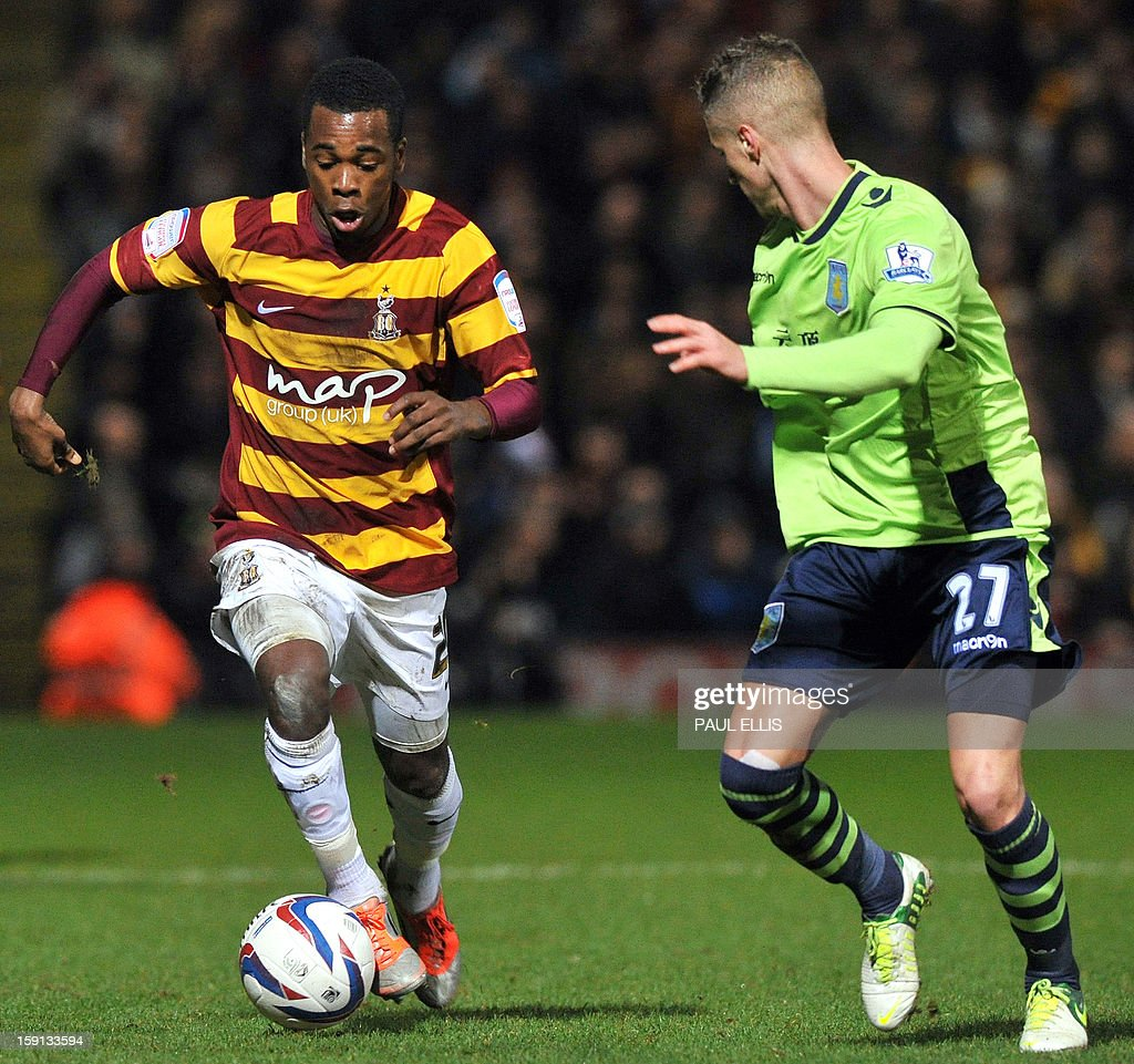 """Bradford City's Jamaican-born English forward Zavon Hines (L) is challenged by Aston Villa's English defender Joe Bennett during the English League Cup first leg semi-final football match between Bradford City and Aston Villa at The Coral Windows Stadium in Bradford, England, on January 8, 2013. Bradford won the match 3-1. AFP PHOTO/PAUL ELLIS USE. No use with unauthorized audio, video, data, fixture lists, club/league logos or """"live"""" services. Online in-match use limited to 45 images, no video emulation. No use in betting, games or single club/league/player publications."""