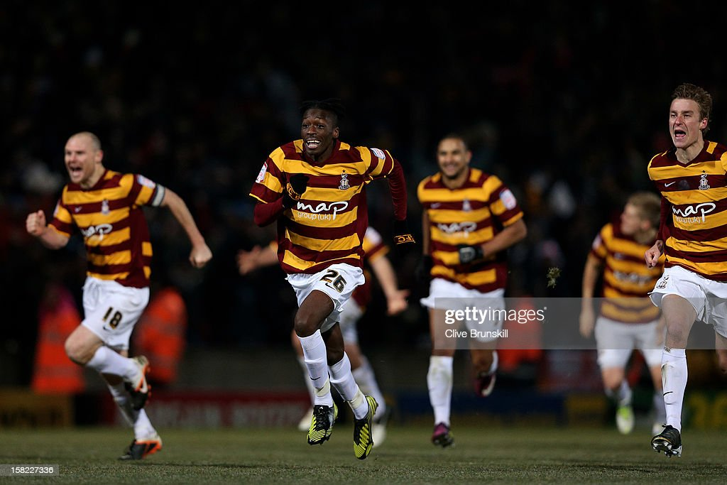 Bradford players celebrate after Goalkeeper Matt Duke of Bradford saves a penalty during the shootout to win the Capital One Cup quarter final match between Bradford City and Arsenal at the Coral Windows Stadium, Valley Parade on December 11, 2012 in Bradford, England.