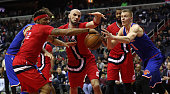 Bradley Beal and Marcin Gortat of the Washington Wizards and Kristaps Porzingis of the New York Knicks go after a loose ball in the first half at...